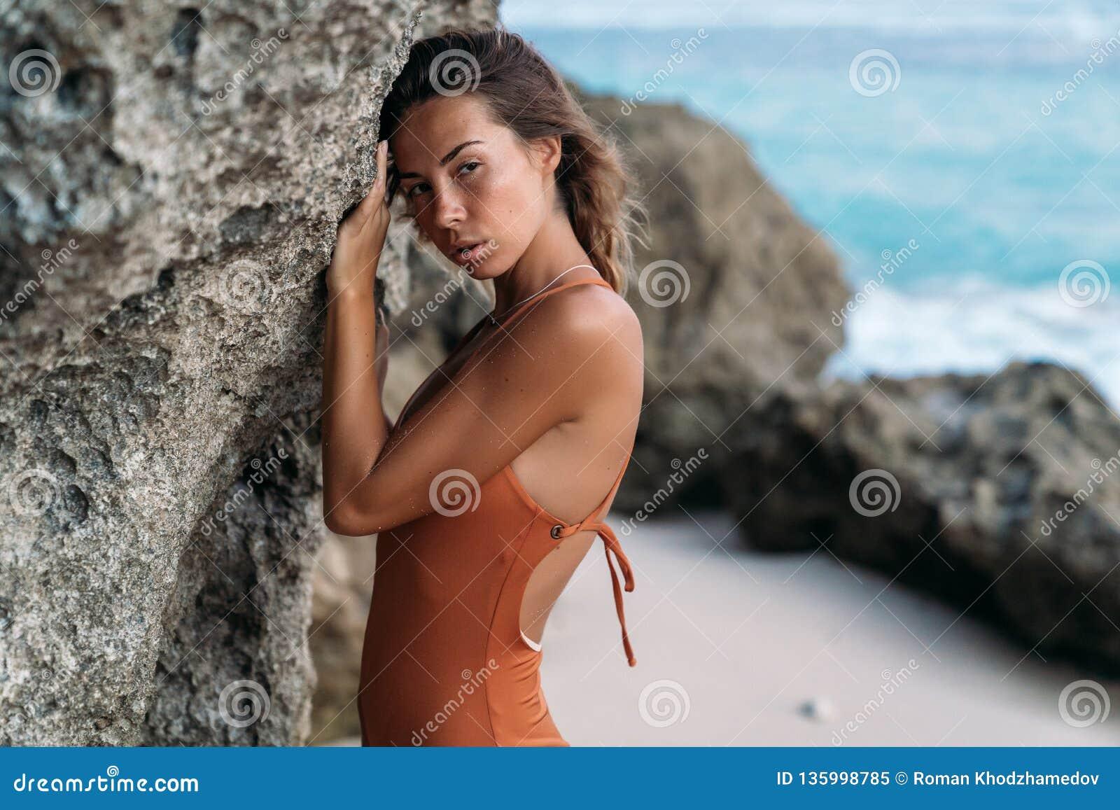 Portrait Of Sensual Tanned Girl In Swimsuit Posing Near Rock On Beach