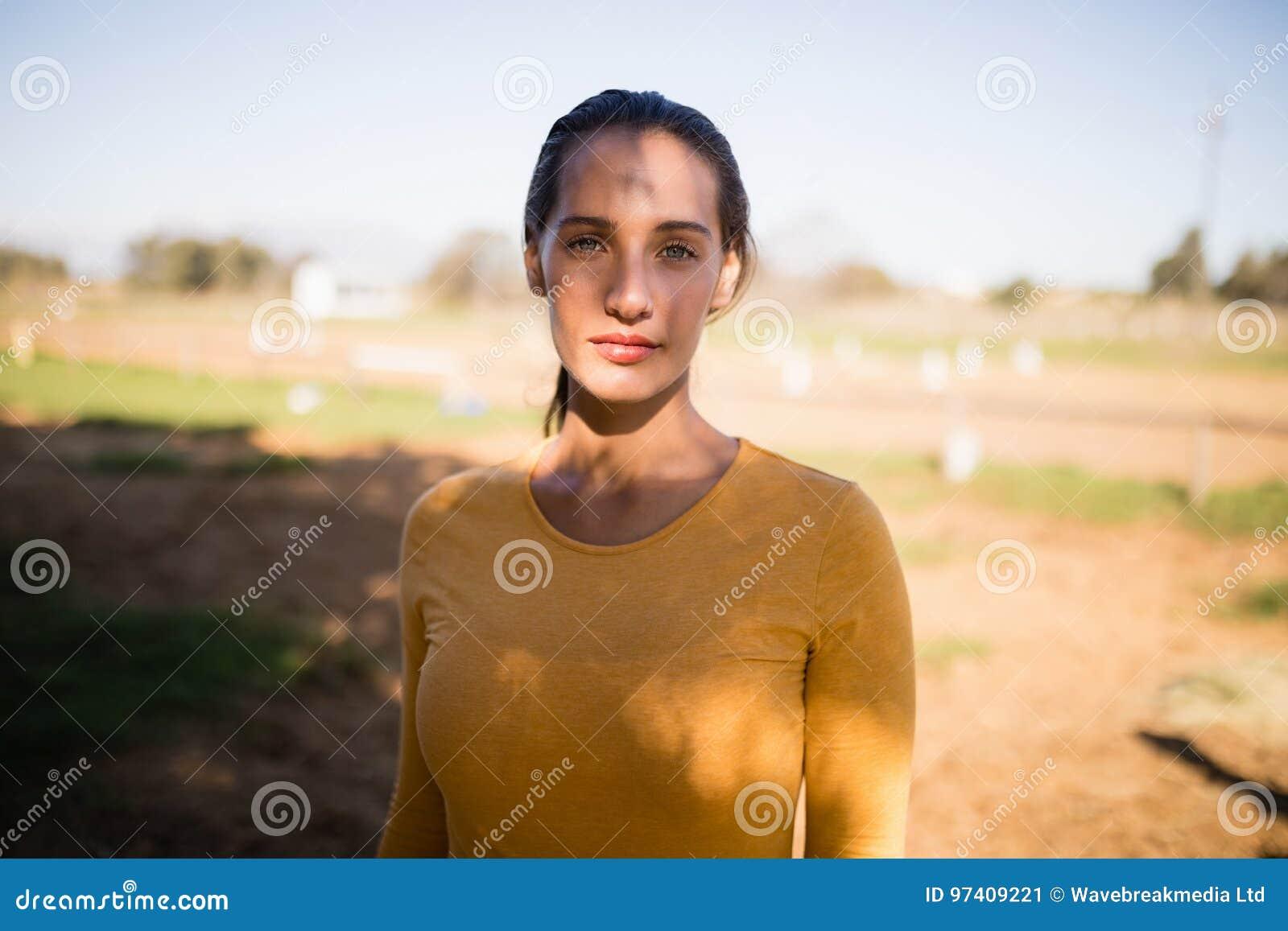 Portrait of serious female jockey standing on field