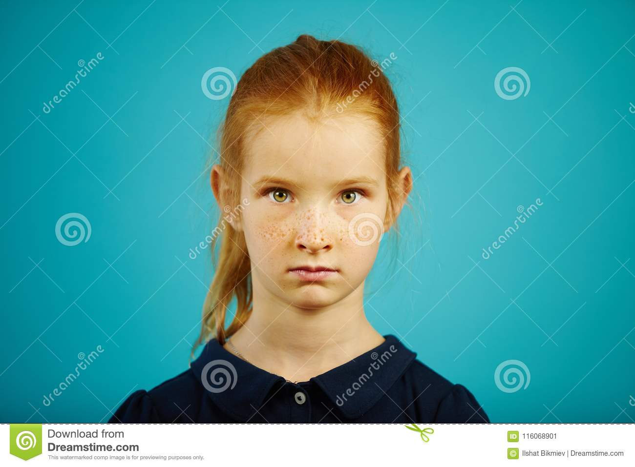 portrait of serious seven year old girl with freckles and red hair