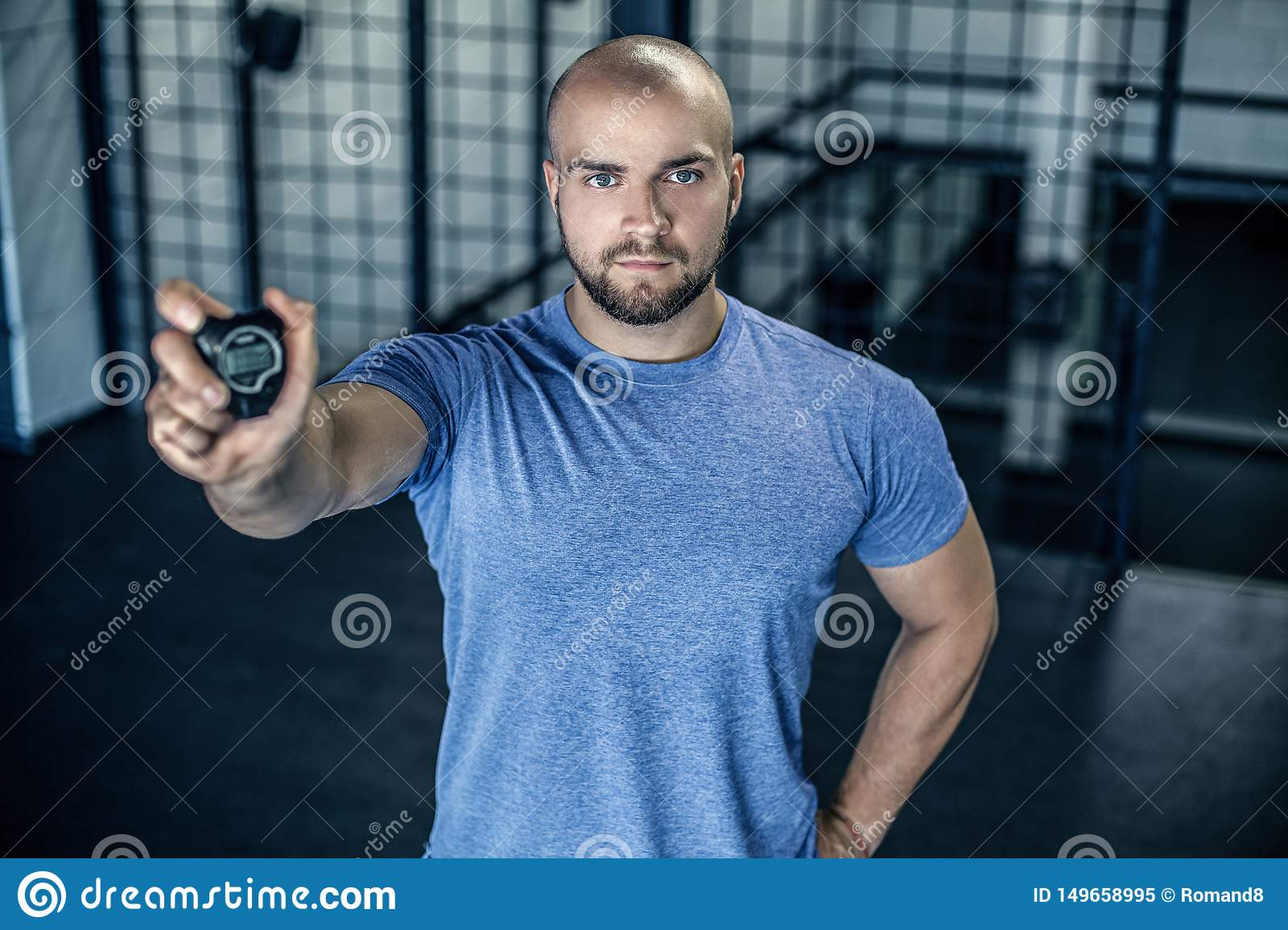 Portrait of a serious sports coach with a bald head. Shows a stopwatch in the camera in the gym. workout was successful.dressed in