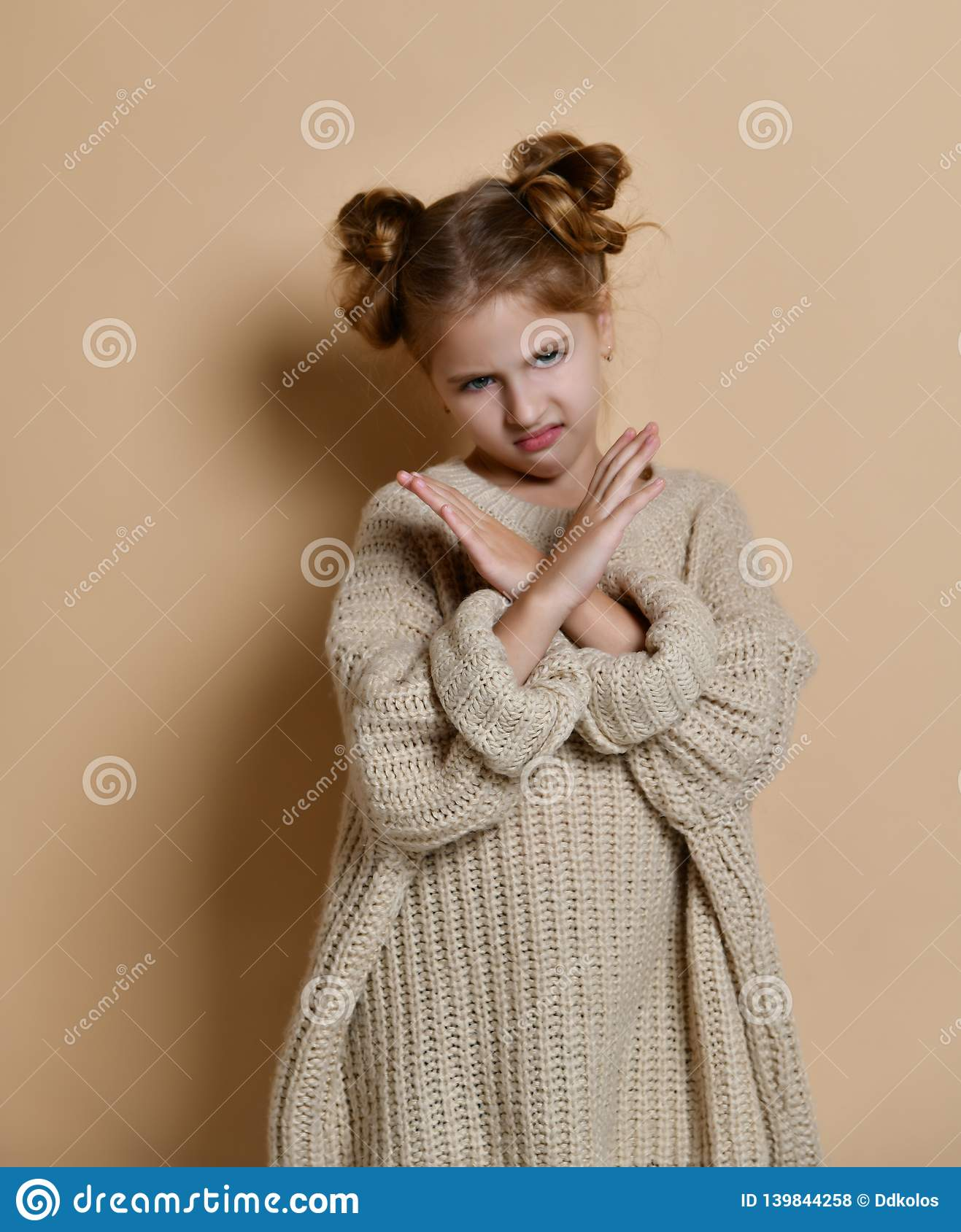 Portrait of serious, unhappy kid girl holding two arms crossed, gesturing no sign, looking away camera