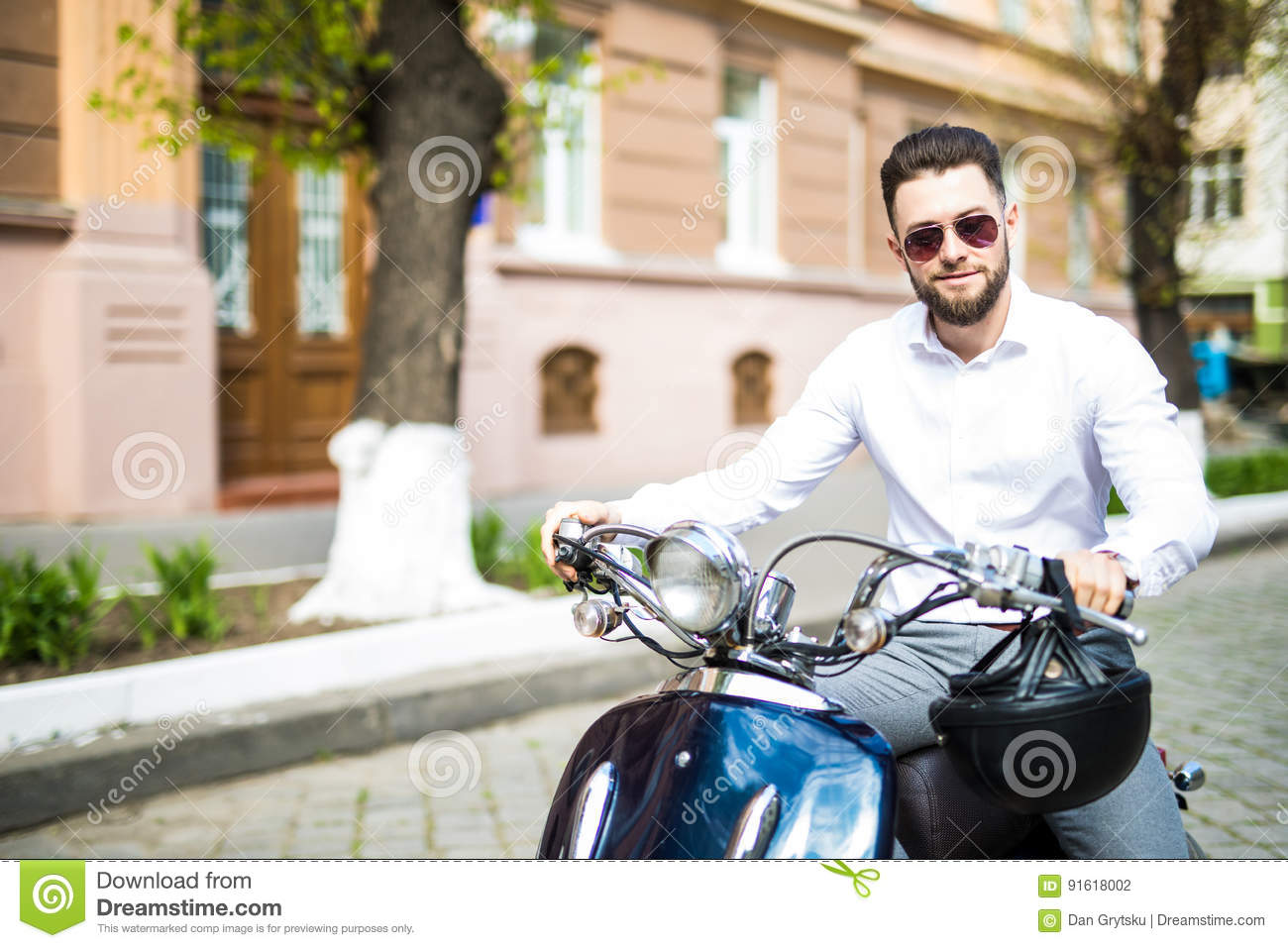Portrait of serious young businessman on motorbike on city street