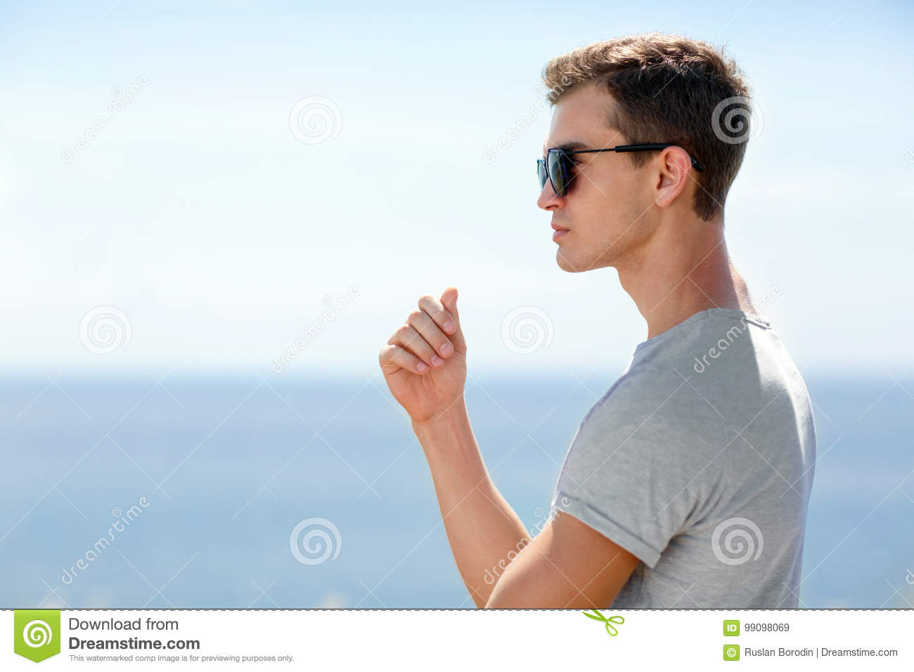 A portrait of a serious young man in sunglasses standing on a blurred sea background. A meditative guy. Copy space.
