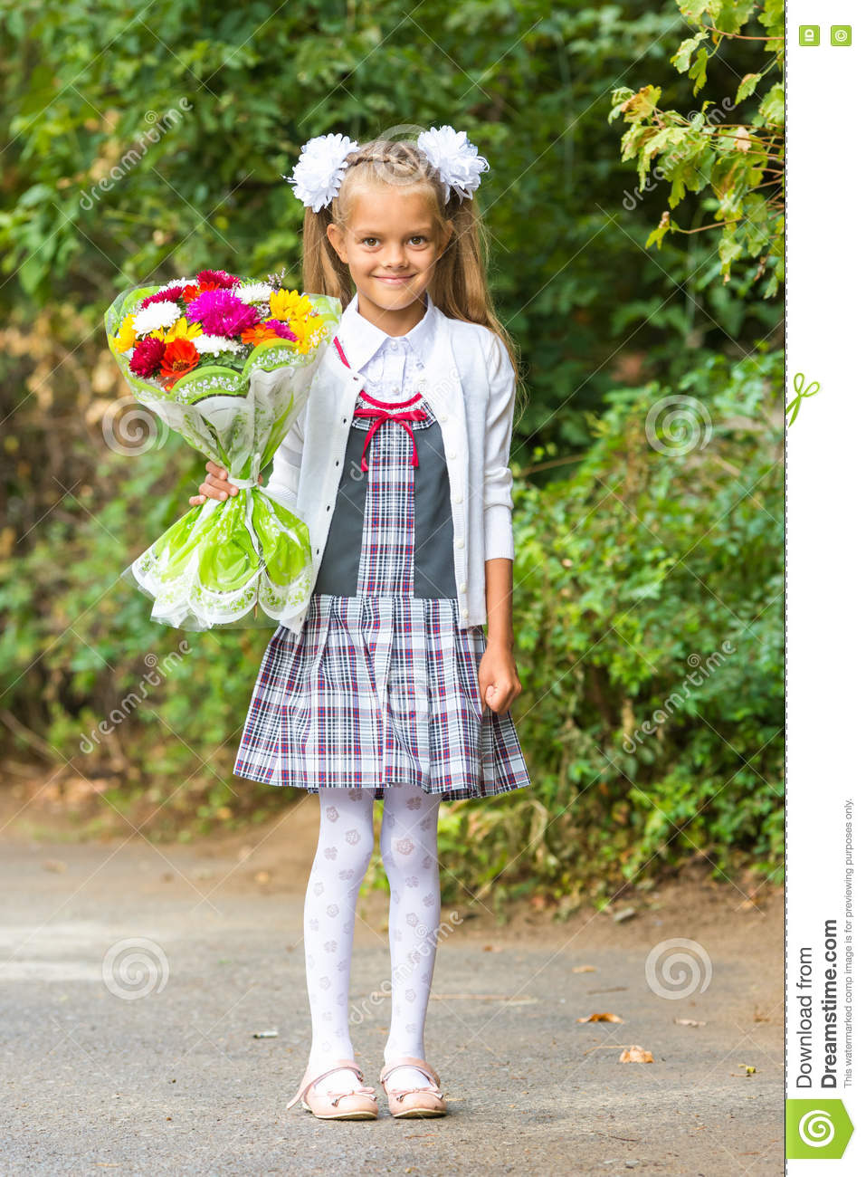 Portrait of seven-year first-grade girl with a bouquet of flowers