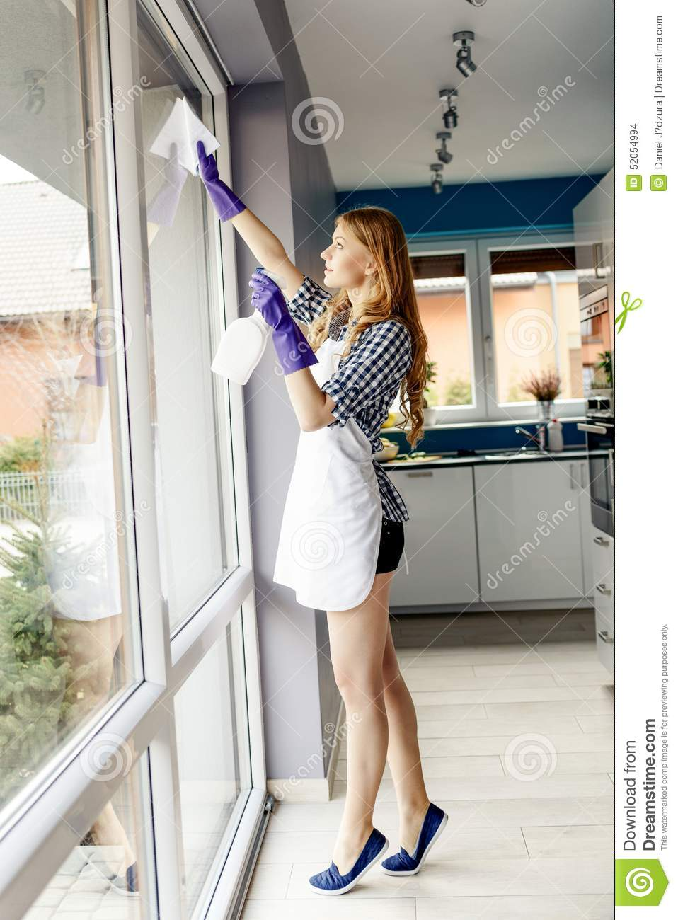 portrait of attractive young woman cleaning windows in the