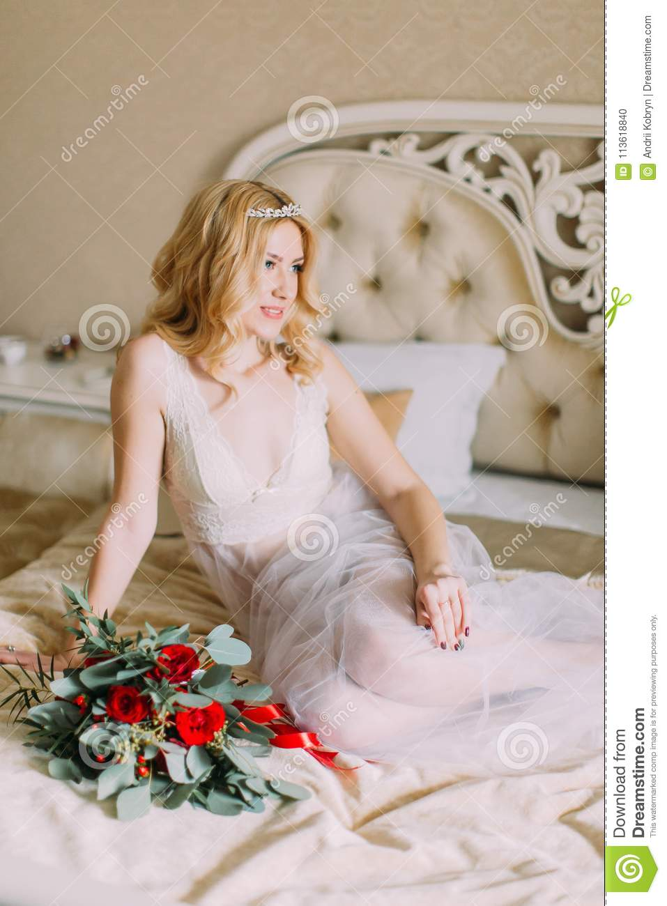 55794ae2707 Portrait of blonde bride in white underwear sitting on bed. Bouquet of red  roses.