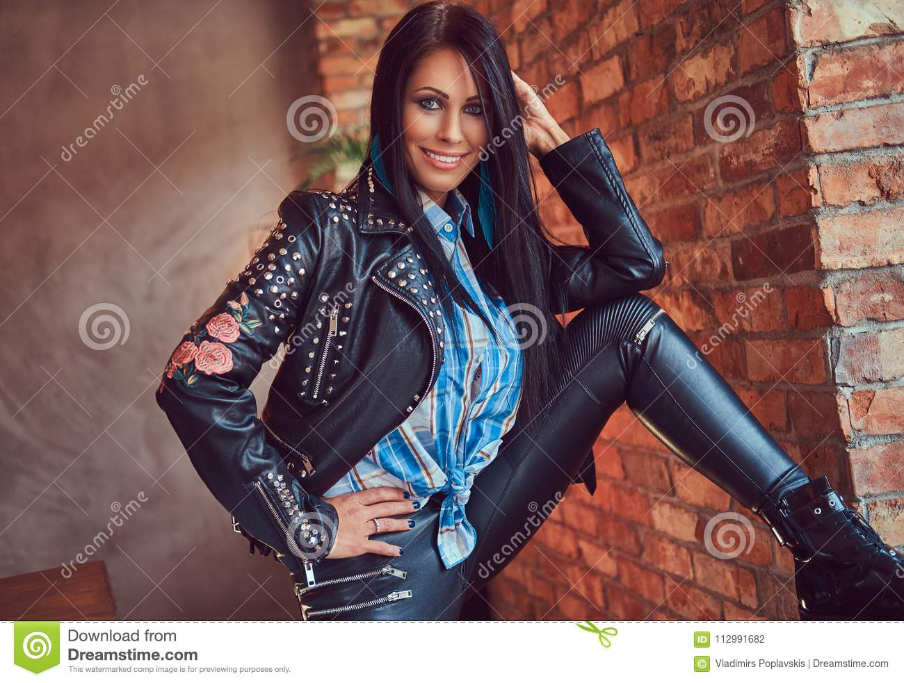 Portrait of a brunette in leather jeans and jacket posing against a brick wall in a room with a loft interior.