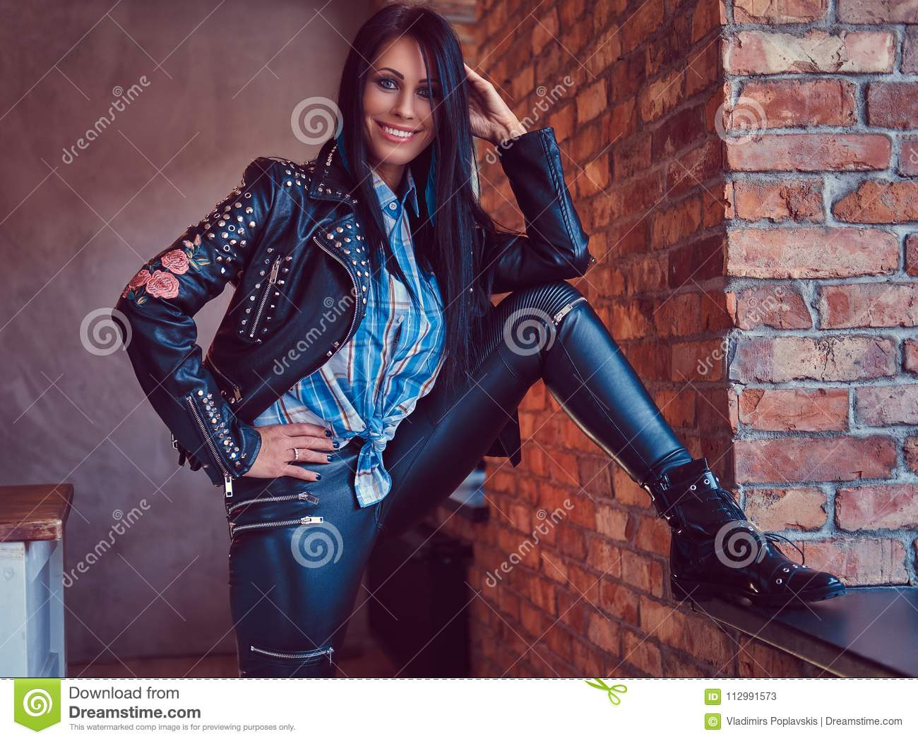 Portrait of a charming brunette posing in a stylish leather jacket and jeans while leaning foot on the window sill.