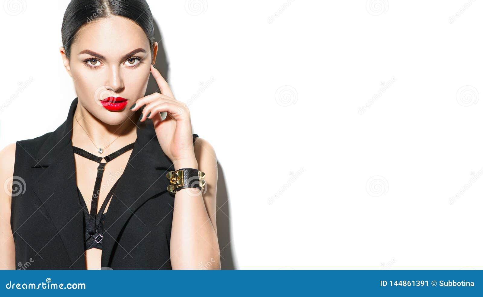 Portrait sexy de jeune femme, sur le fond blanc Fille modèle de brune séduisante dans des vêtements sexy noirs, accessoires de