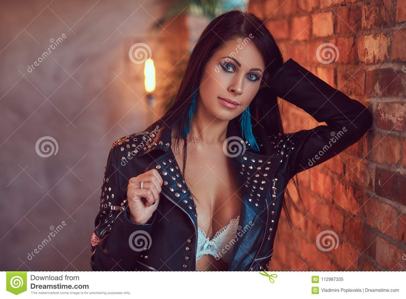 Portrait of a sensual brunette posing in underwear and stylish leather jacket leaning against a brick wall.