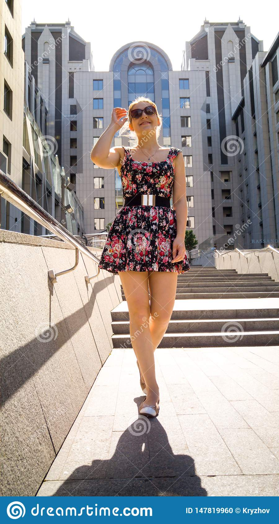 2cc419ee1d15 Portrait of sexy woman in short dress posing against modern building made  of concrete and glass in sun light rays