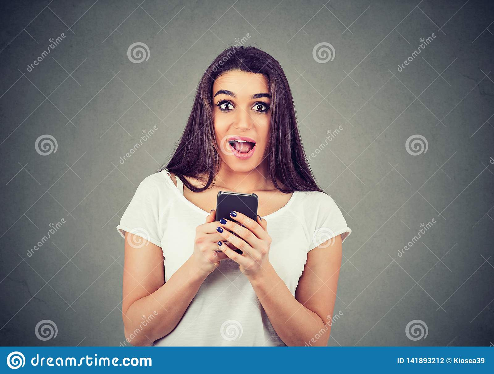 Portrait of a shocked young woman holding a mobile phone looking at camera