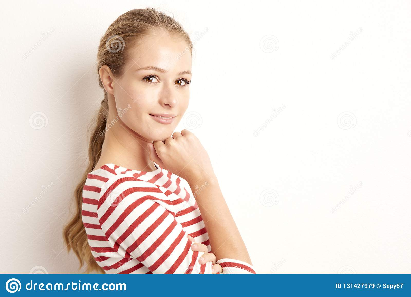 Studio portrait of pretty young woman lookig at camera and smiling while standing at isolated white background and playing with