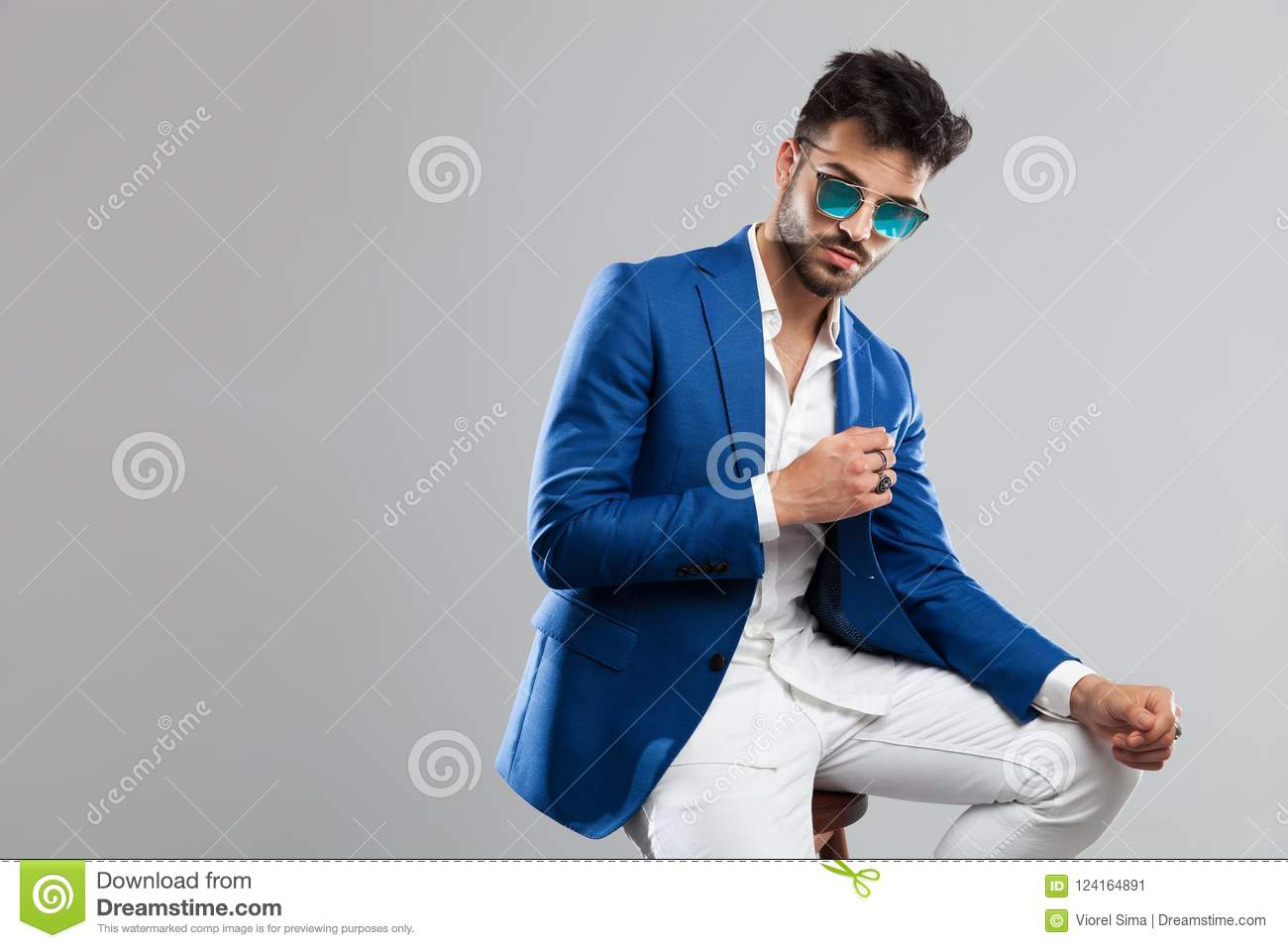 8c69e3e79b55 Portrait of smart casual man wearing sunglasses resting his elbow on his  knee while sitting on light grey background