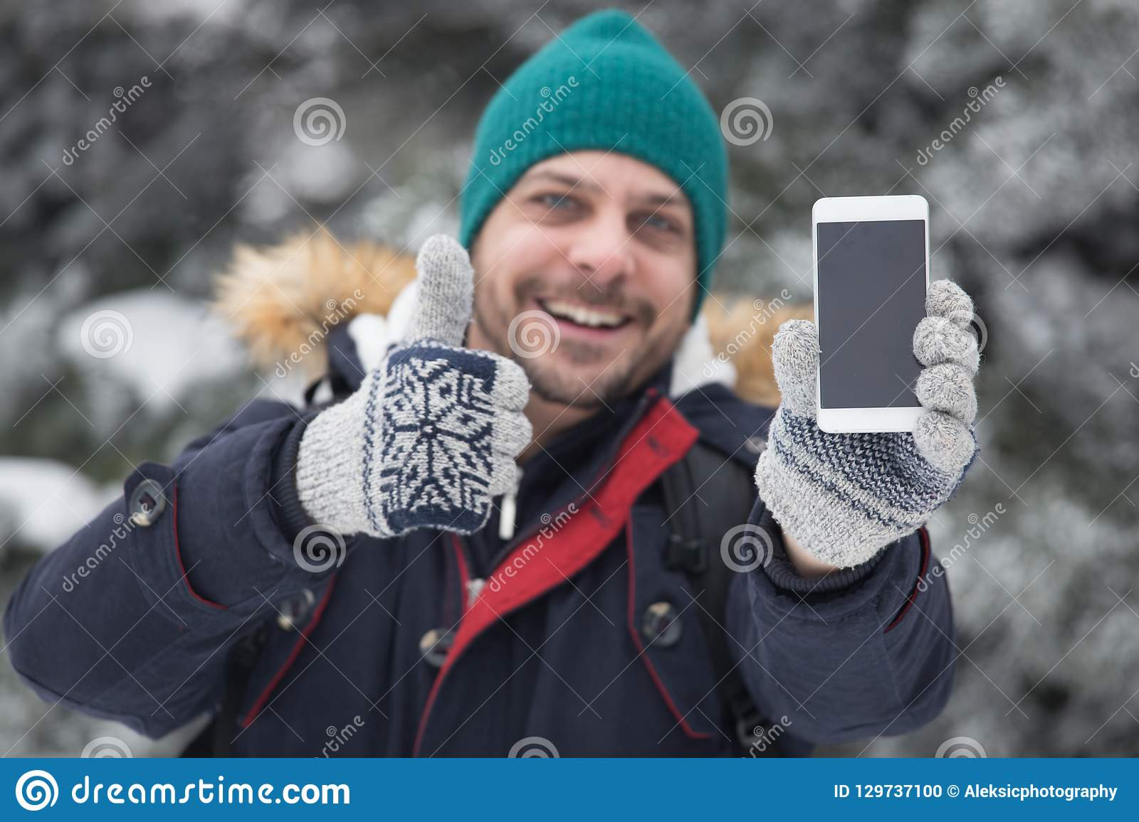 Portrait of smile man who holding smart phone and thumb up. Holiday concept