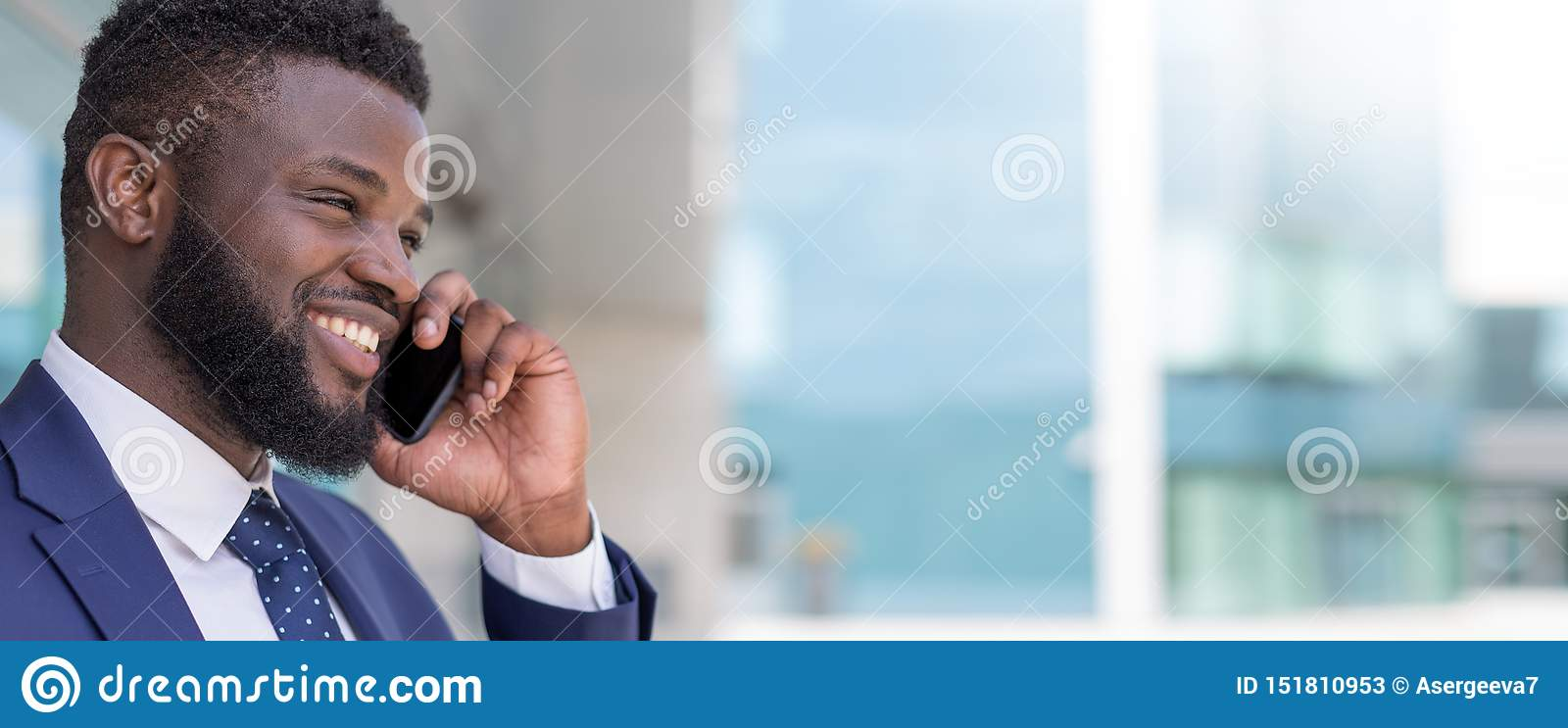 Portrait of smiling african businessman talking by phone outside with copy space