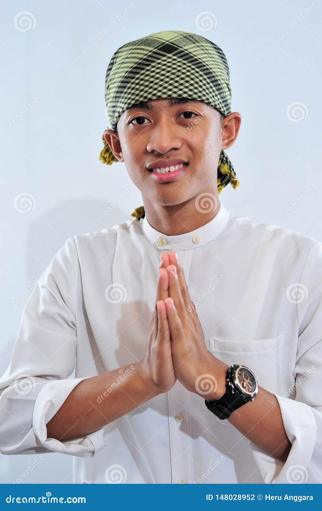 Portrait of smiling asian muslim man welcoming you