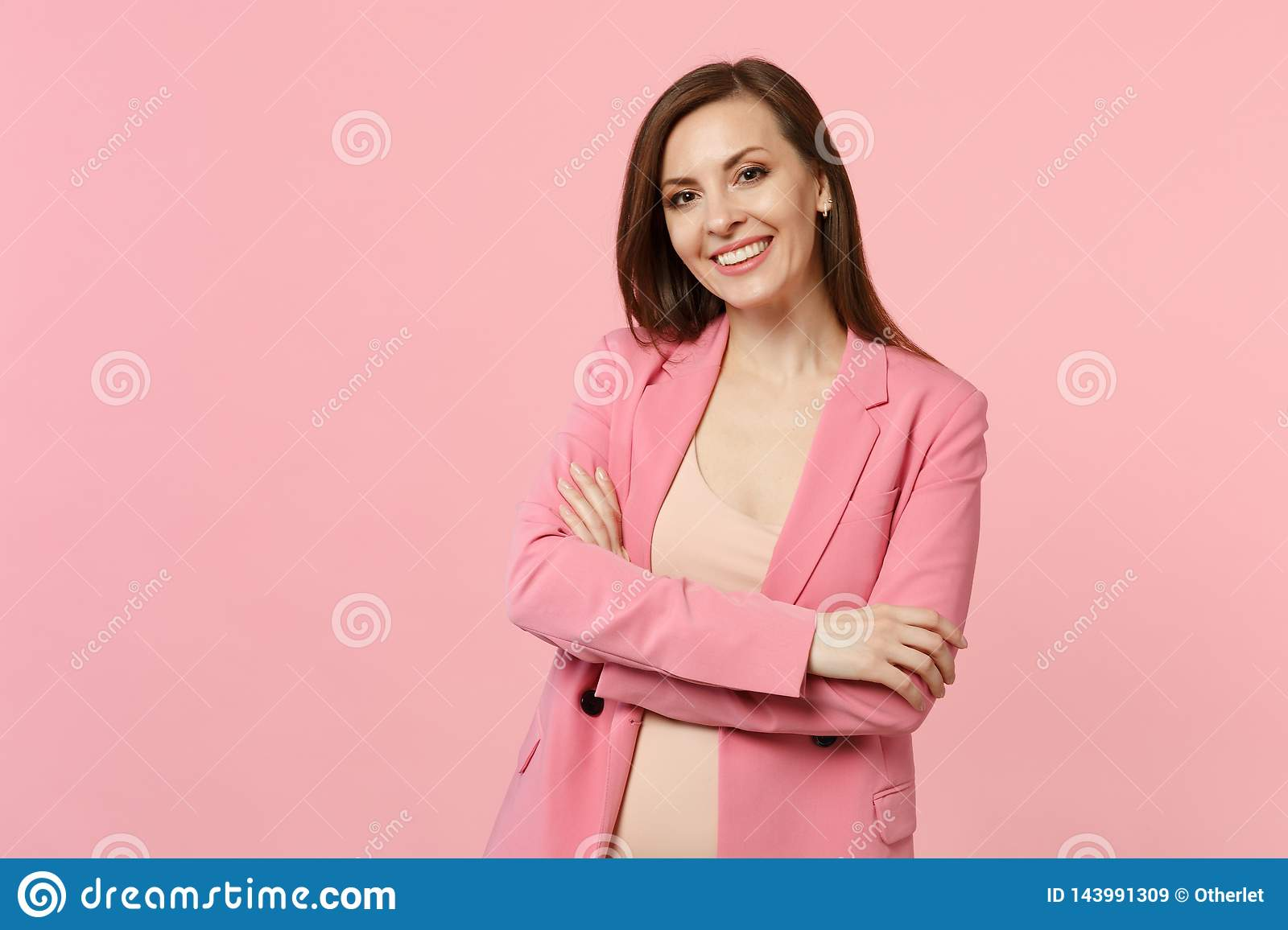 Portrait of smiling beautiful young woman in jacket standing, holding hands crossed isolated on pastel pink wall