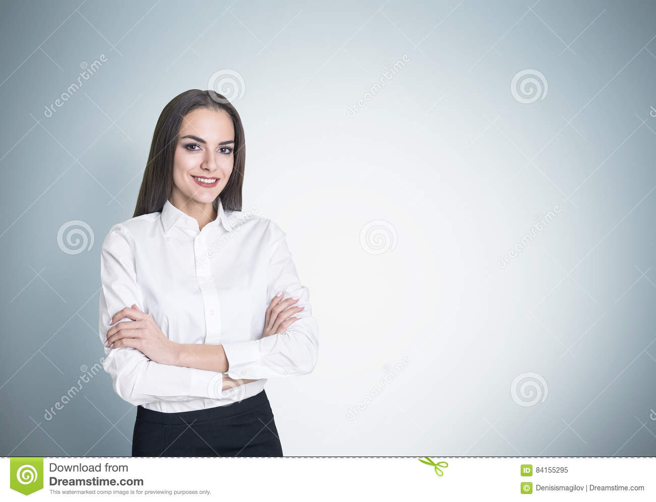 Portrait of a smiling businesswoman standing with her arms crossed near a gray wall and looking at the viewer with confidence.