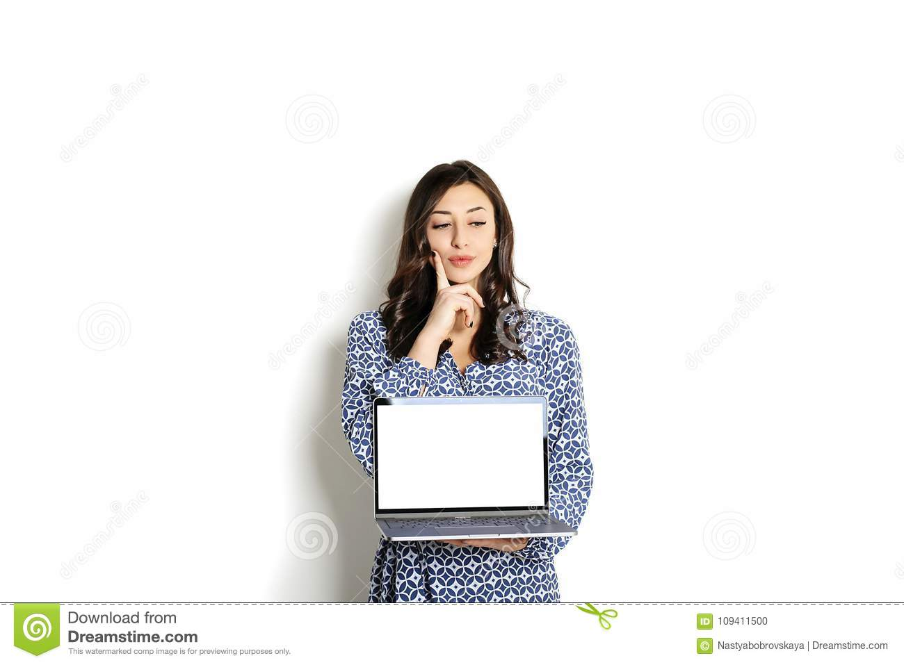 Portrait, smiling confident pretty woman long sleeve dress, holding grey laptop device and typing while standing against solid whi