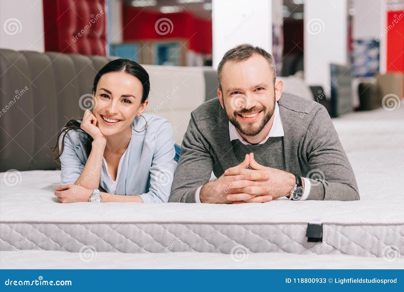 portrait of smiling couple lying on mattress
