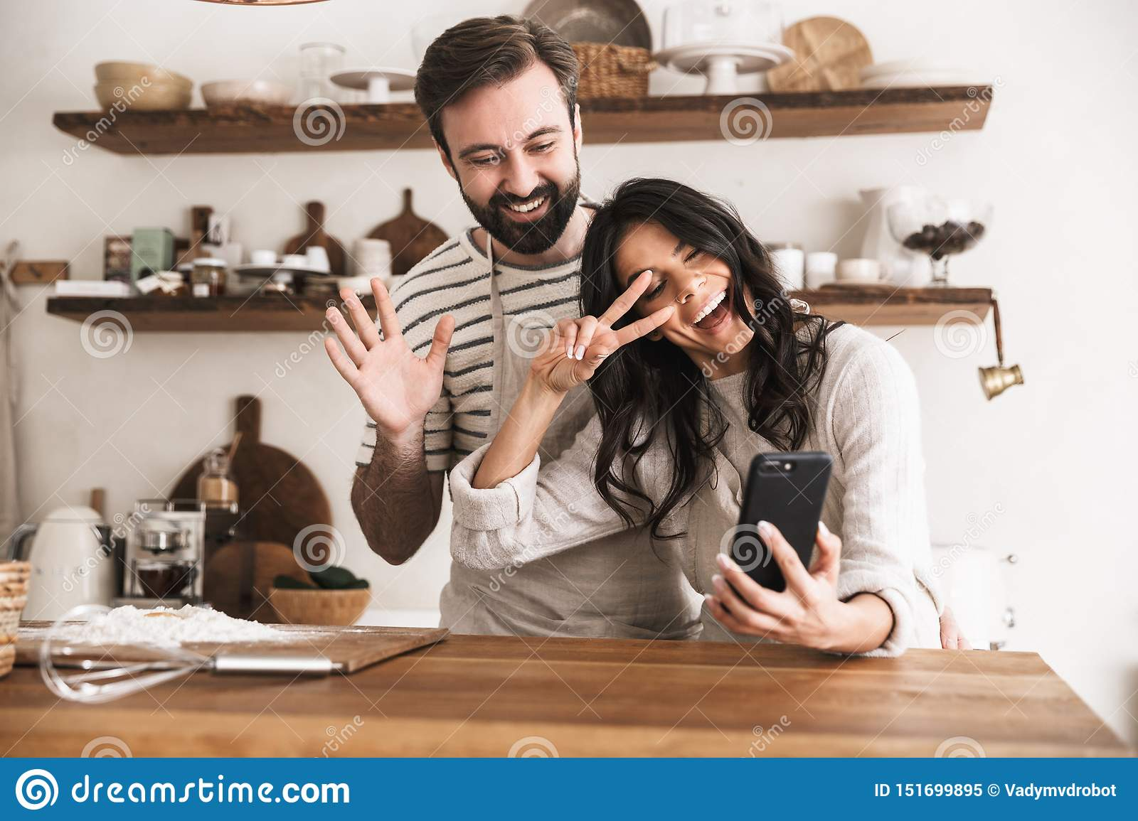 Portrait of smiling couple hugging together and holding smartphone while cooking in kitchen at home