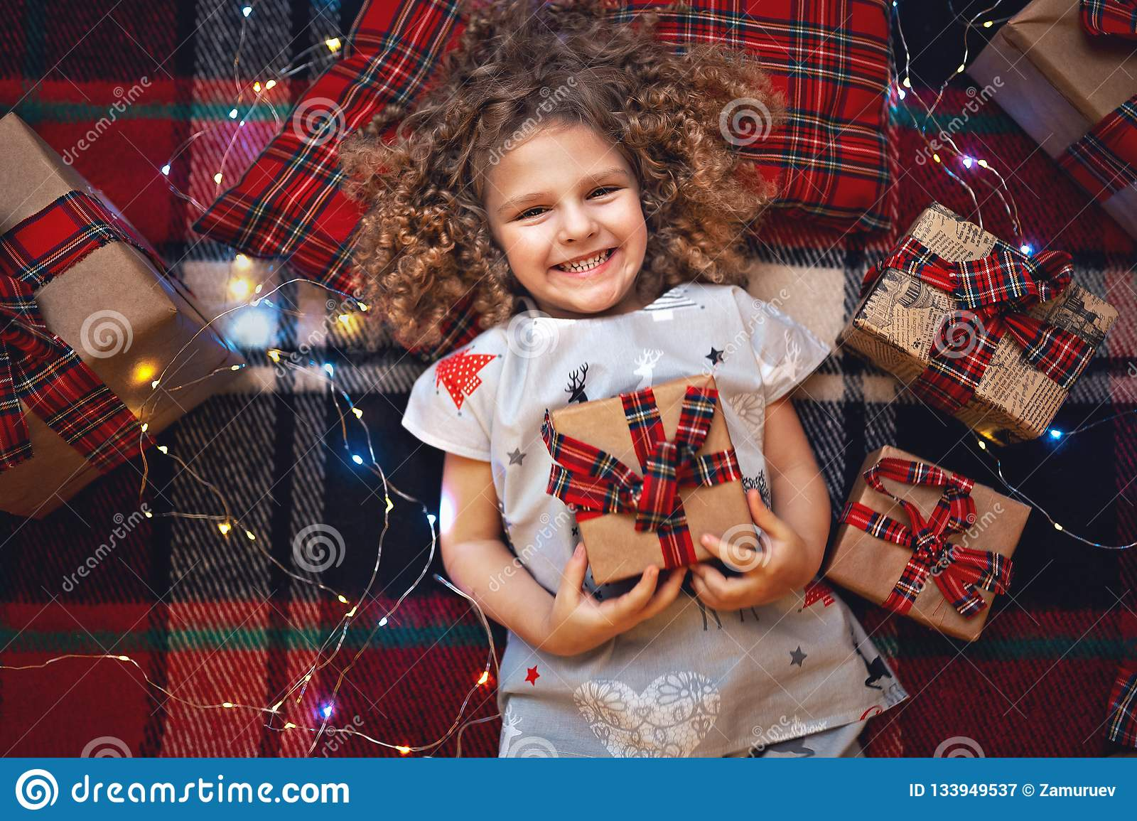 Portrait of smiling cute little child in holiday christmas pajamas holding gift box. Top view.