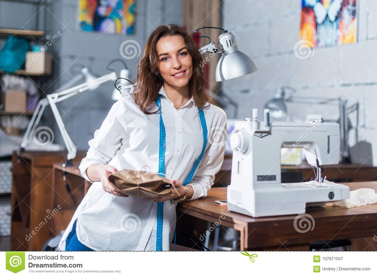 Portrait Of Smiling European Fashion Designer Standing Next To Sewing Machine Holding A Gift Packed In Craft Paper In Stock Image Image Of Owner Garment 107671047