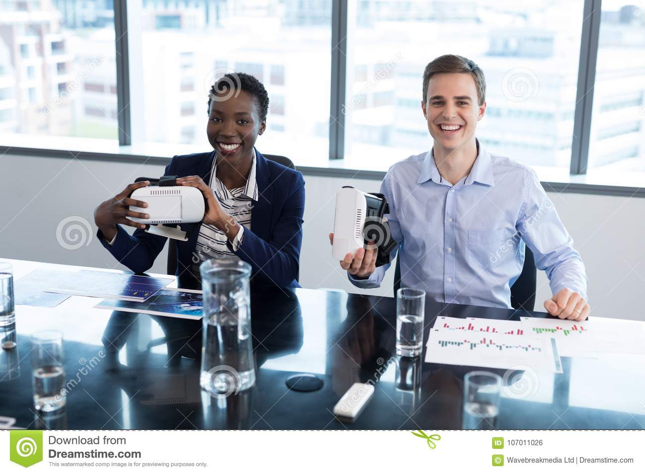 Portrait of smiling executives holding virtual reality headset