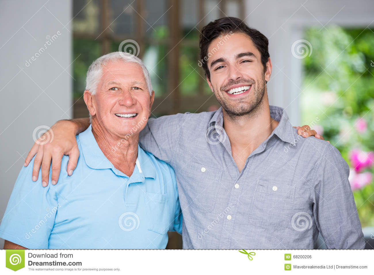 Portrait of smiling father and son with arm around