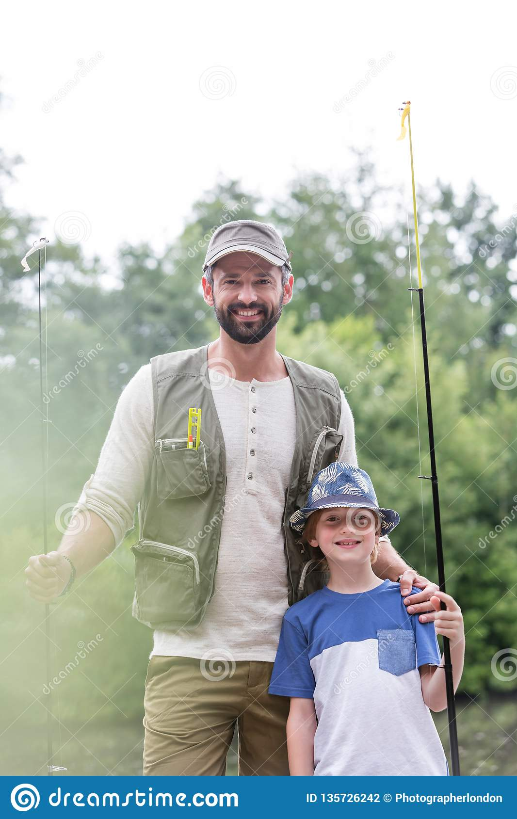 Portrait of smiling father and son standing with fishing rods against trees