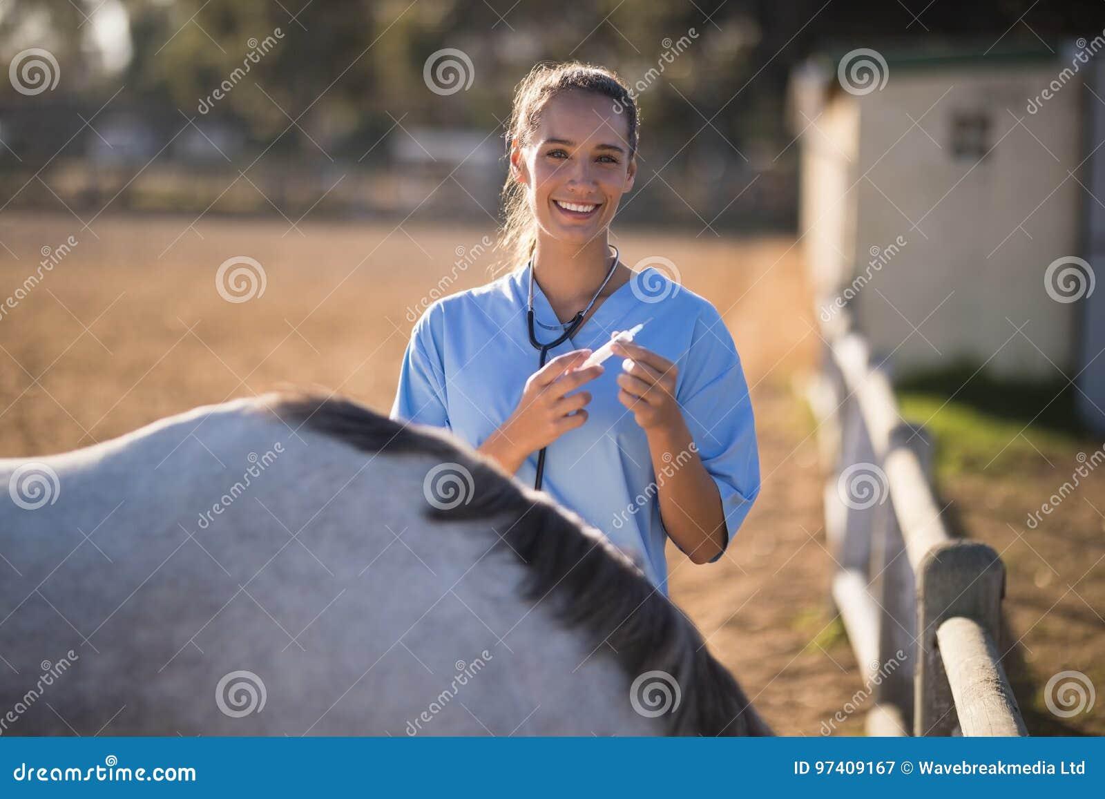 Portrait of smiling female vet holding syringe