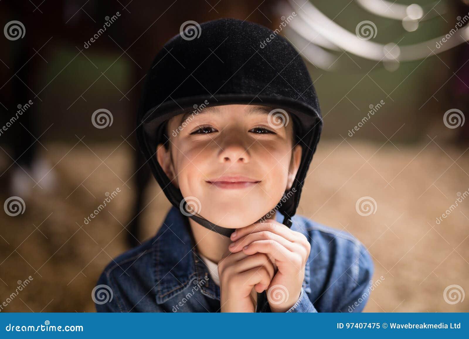 Portrait of smiling girl fastening helmet