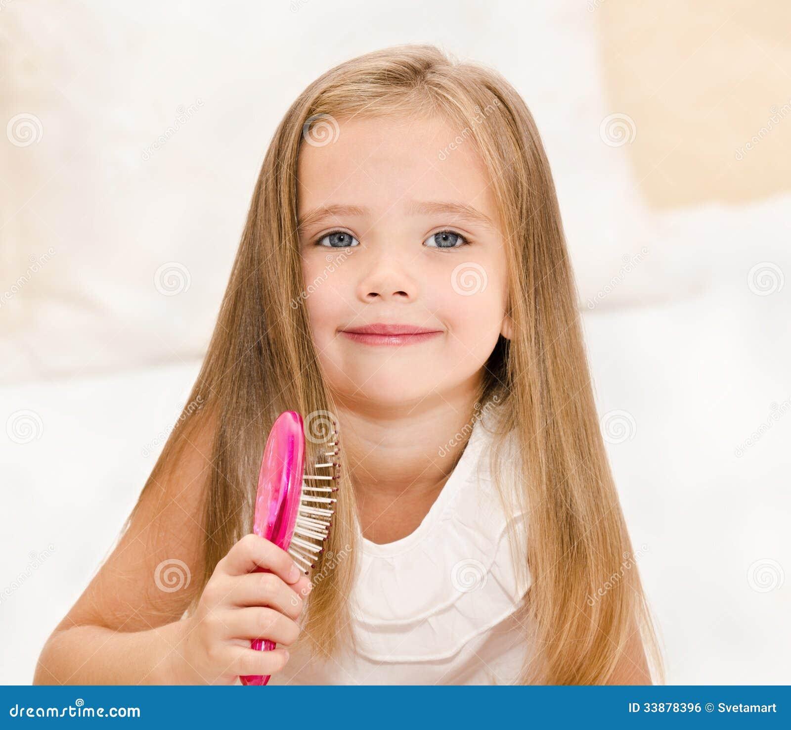 Portrait Of Smiling Little Girl Brushing Her Hair Stock