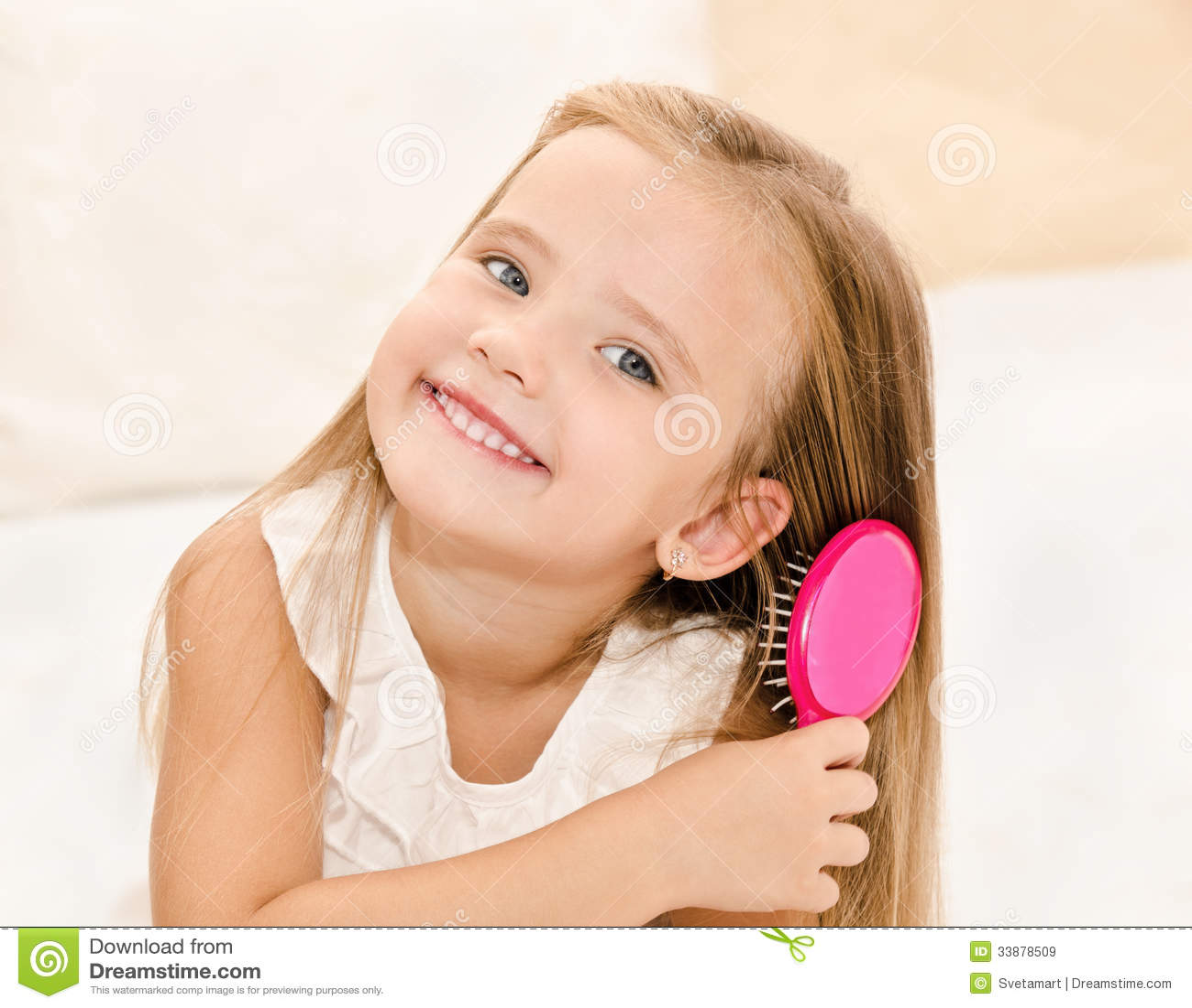 Portrait of smiling little girl brushing her hair royalty free stock