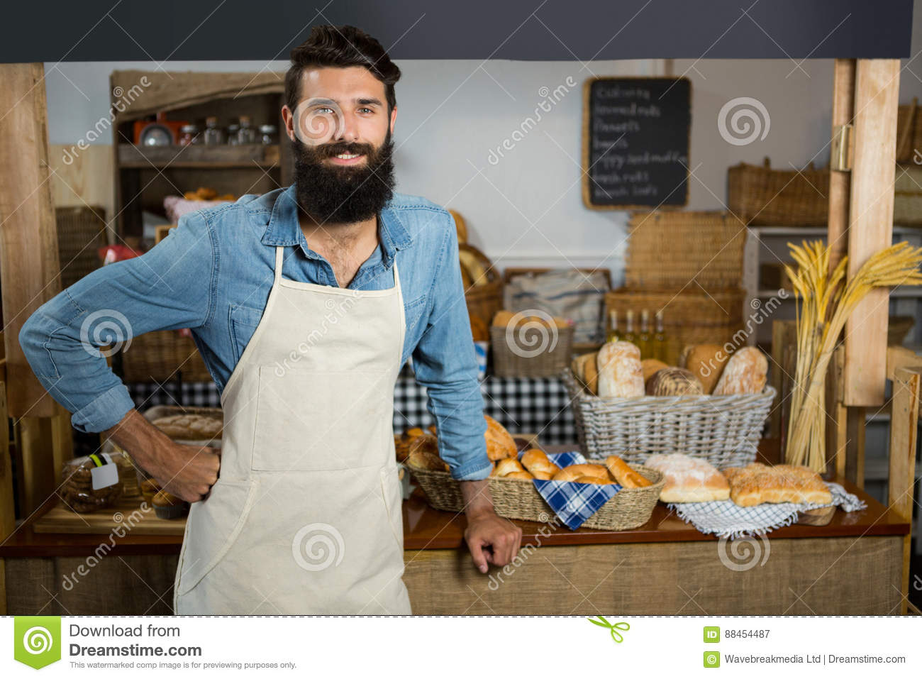 Portrait of smiling male staff standing with hands on hip at counter
