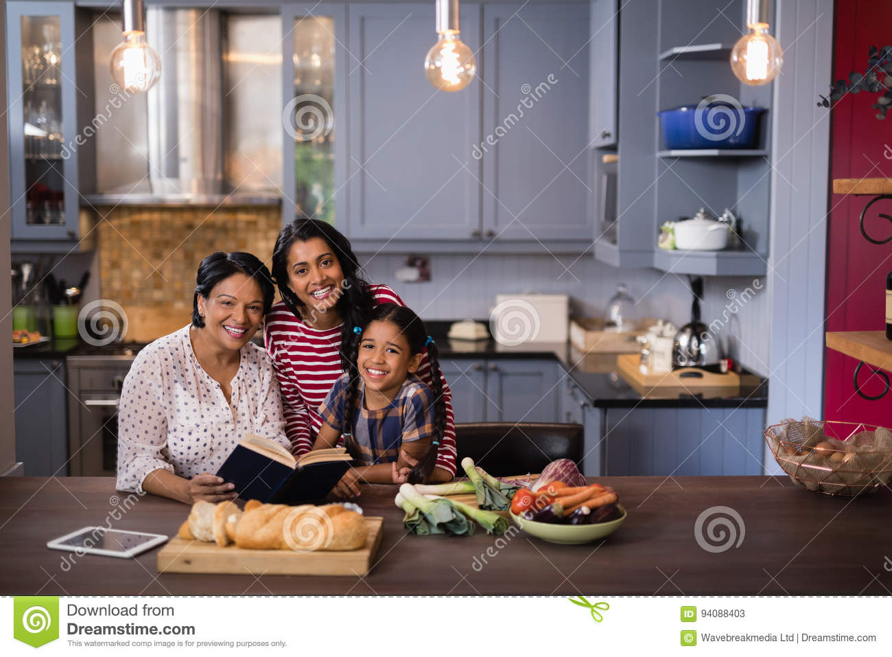 Portrait of smiling multi-generation family sitting in kitchen