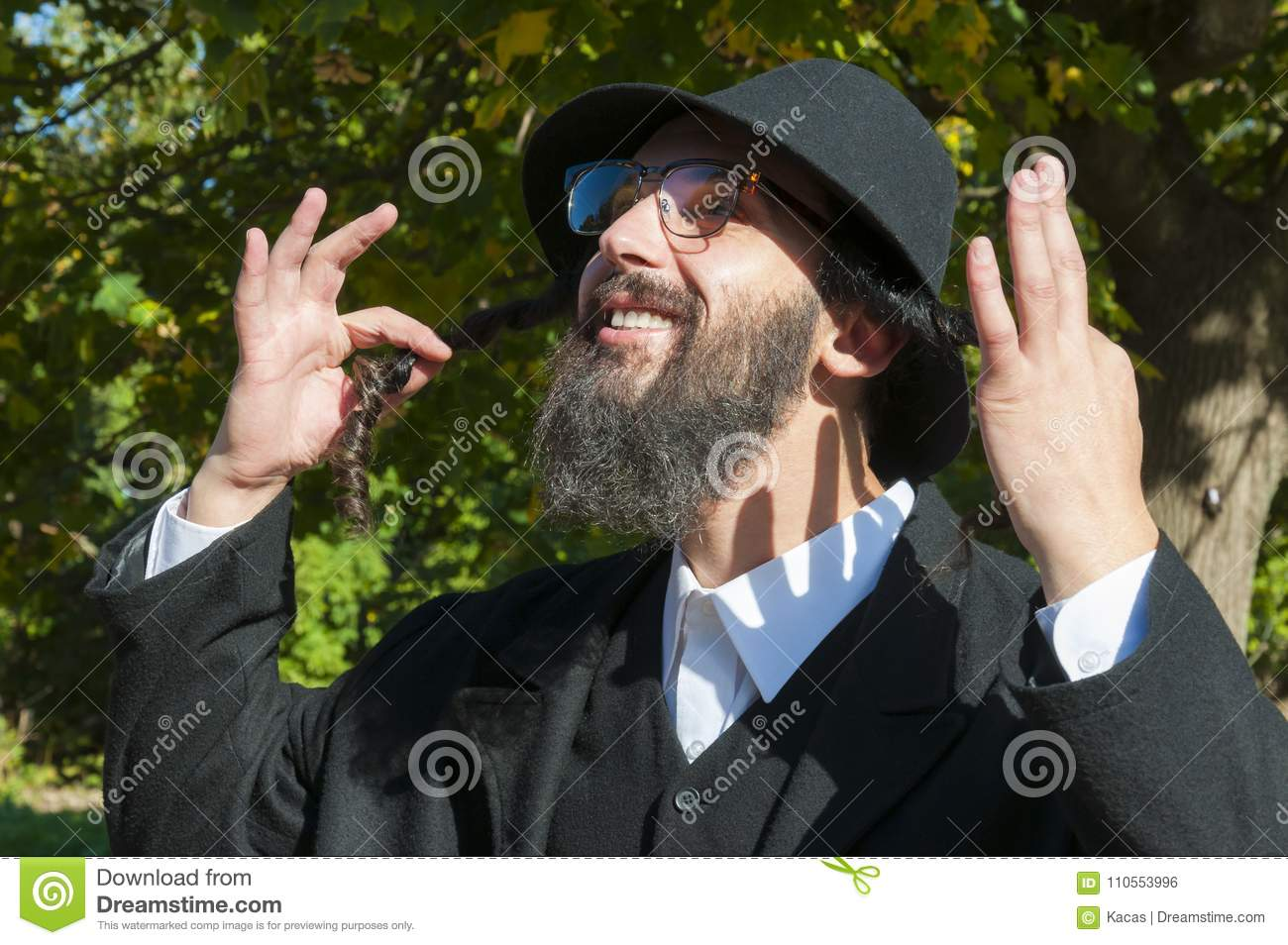 ec6b9cba4a7 Outdoor sunny portrait of a young happy orthodox Jewish man with eyeglasses  and black beard holding payot