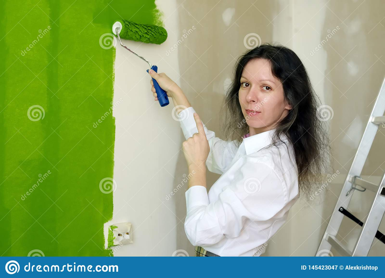 Portrait of a smiling pretty young woman is painting green interior wall with roller in a new home and pointing on her work