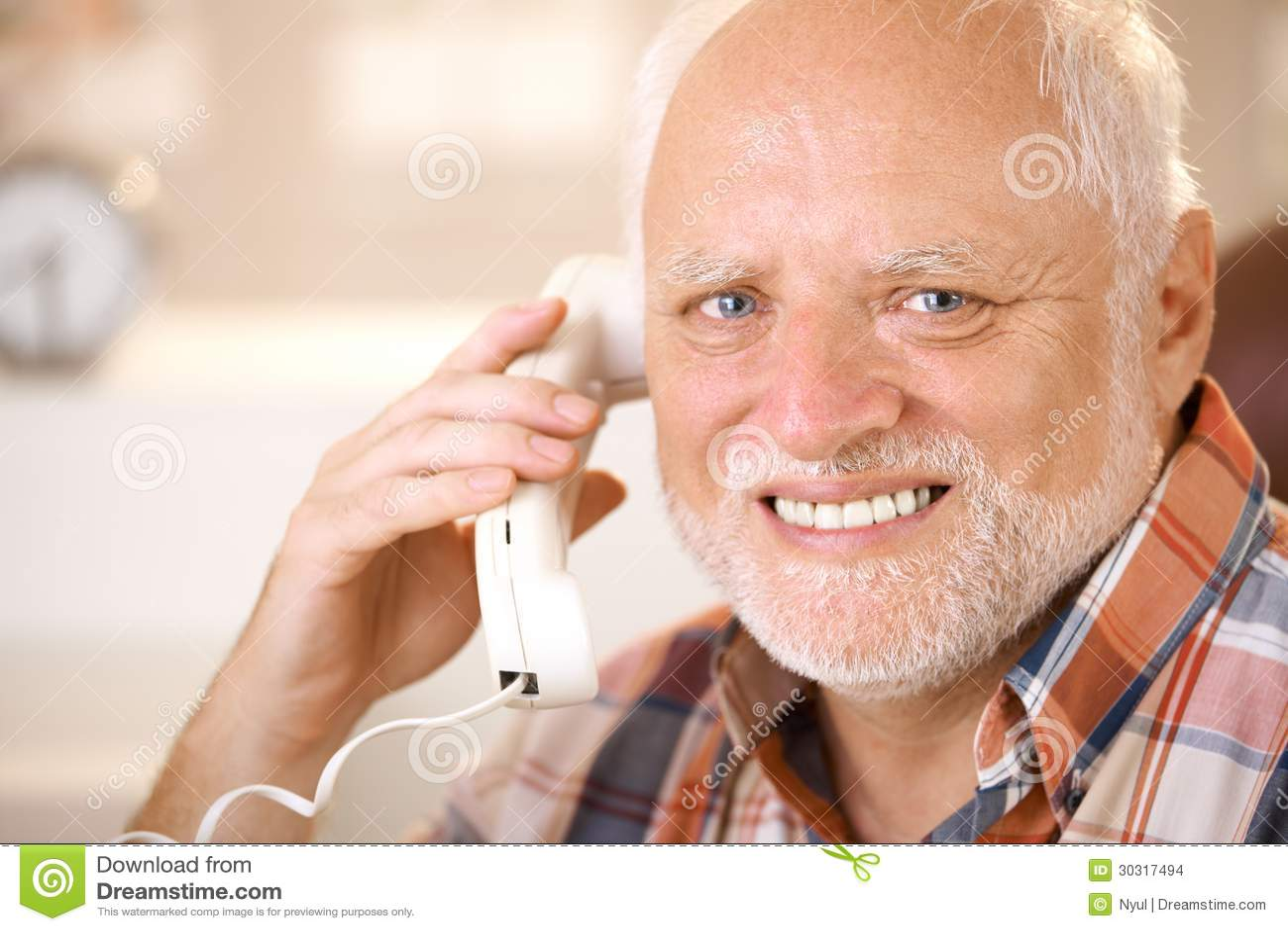 Portrait of smiling senior using landline phone stock for People s choice 65