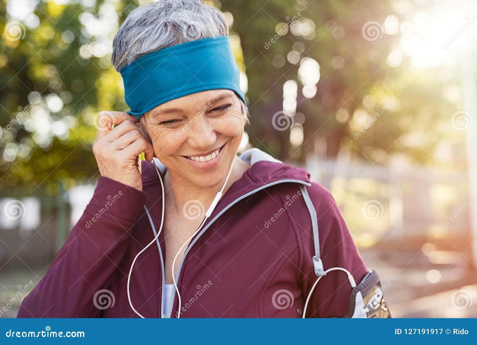 Mature woman adjusting earphones before running