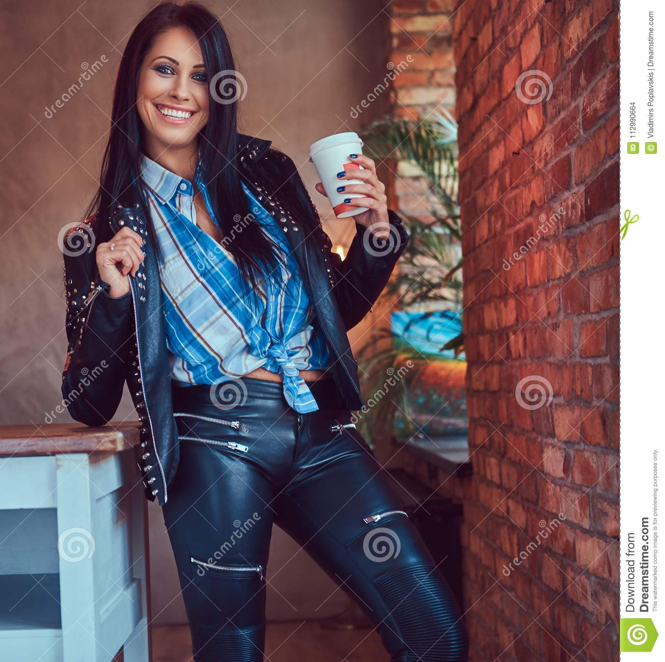 Portrait of a smiling sensual brunette posing in a stylish leather jacket and jeans leaning on a table holds a cup