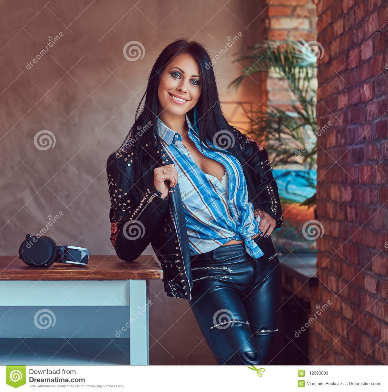 Portrait of a smiling sensual brunette posing in a stylish leather jacket and jeans leaning on a table in a studio