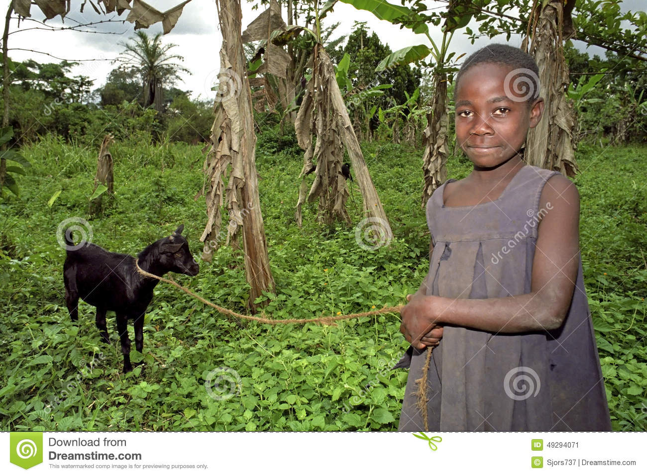 Portrait of smiling Ugandan goatherd with goat