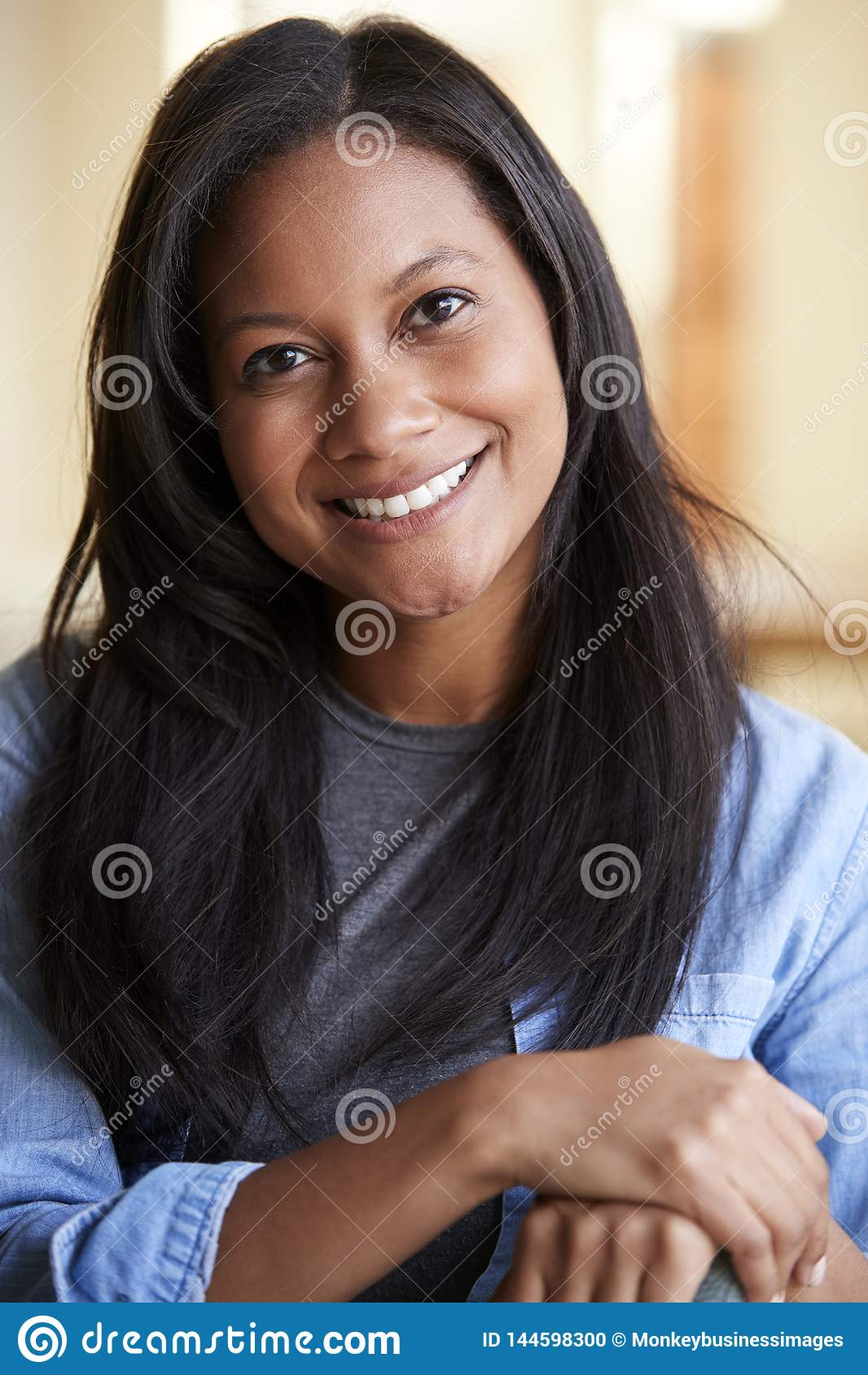 Portrait Of Smiling Woman Relaxing On Sofa At Home