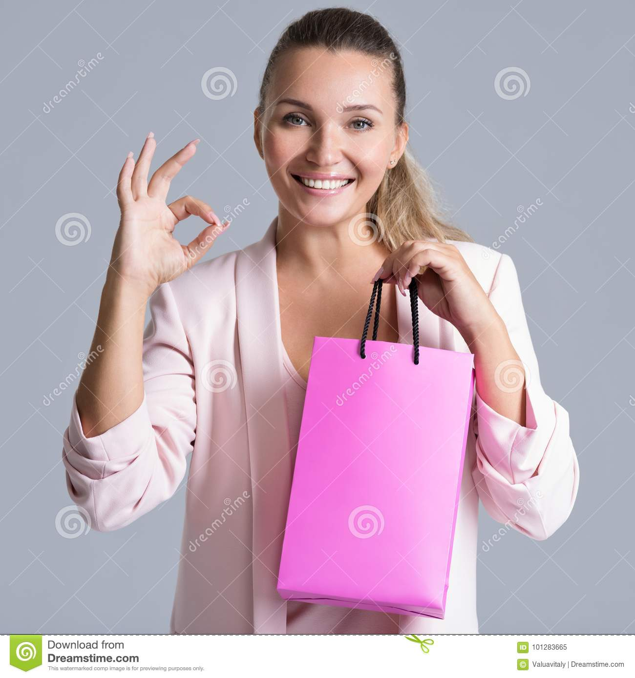 Portrait of a happy smiling woman with pink shopping bag.