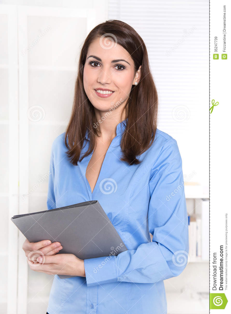 portrait of a smiling young businessw in a blue blouse is go portrait of a smiling young businessw in a blue blouse is go