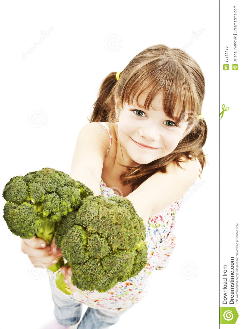 Portrait of a smiling young girl holding broccoli