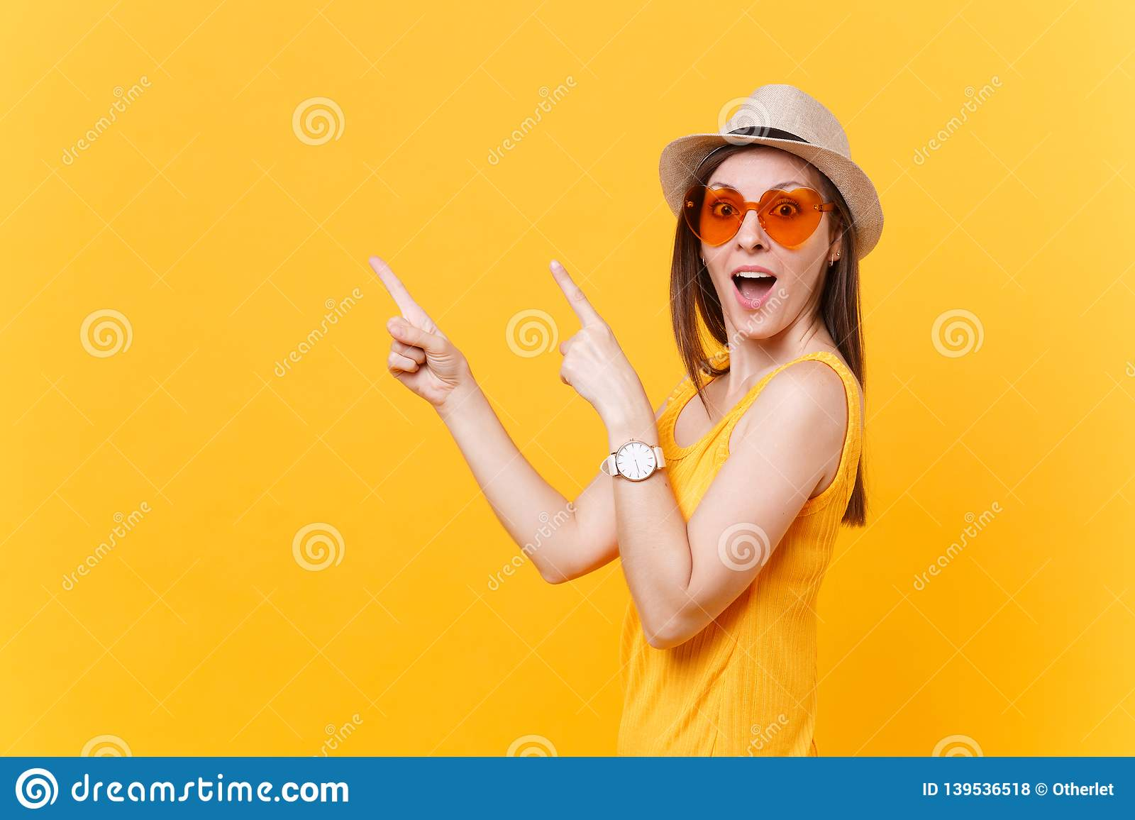 Portrait of smiling young woman in straw summer hat, orange glasses pointing index fingers aside copy space isolated on