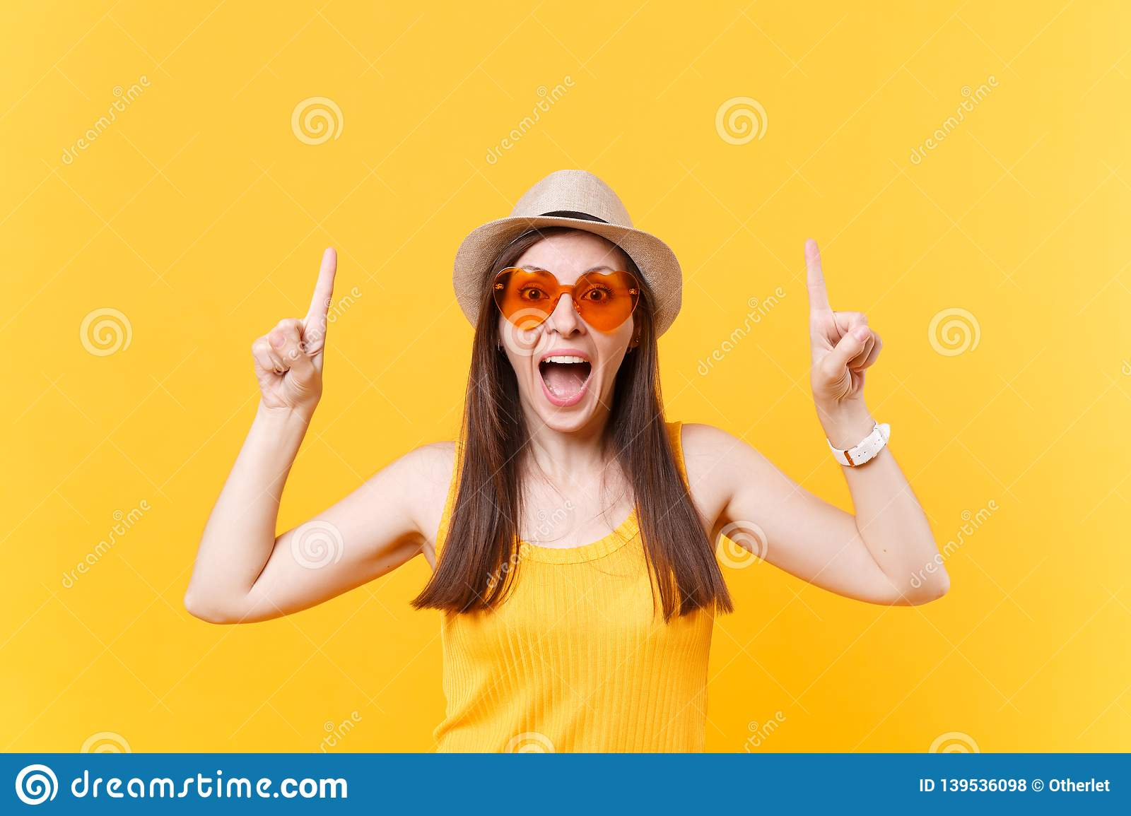 Portrait of smiling young woman in straw summer hat, orange glasses pointing index fingers up on copy space isolated on